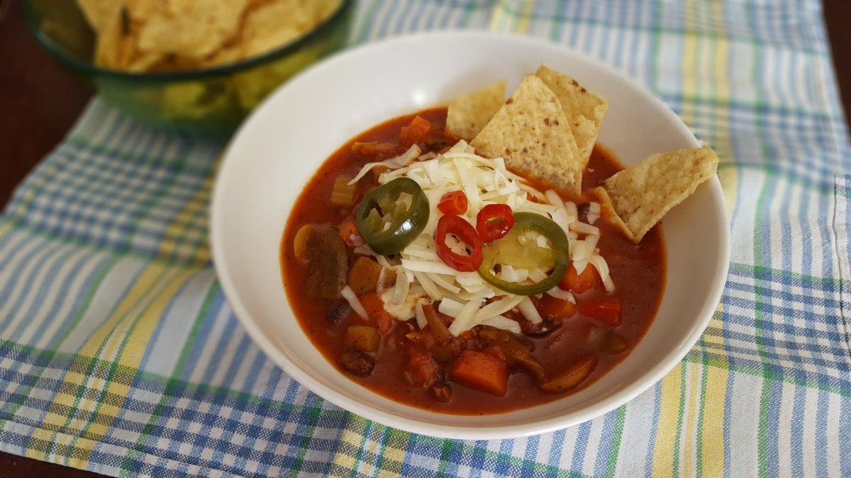 vegetarian chili with carrots, black beans, poblano peppers, topped with cheddar cheese and pickled jalapenos