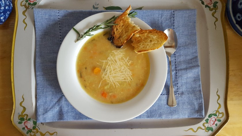 pureed soup made with white beans, lamb, white wine, carrots, celery, onions and garlic served with crusty bread and Parmesan cheese with a rosemary garnish