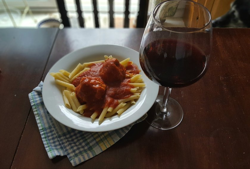 turkey meatballs in red sauce over pasta with a glass of red wine