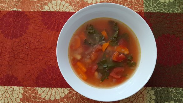 a bowl of vegetable soup with carrots, tomatoes, onions and fresh kale