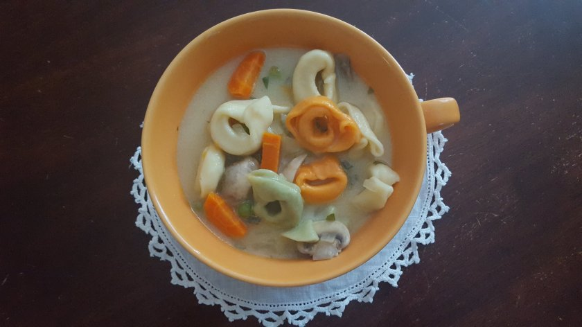 cup of soup with colored cheese tortellini and chicken broth