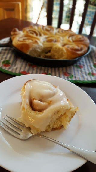 Cast-Iron Cinnamon Bun with cream cheese frosting on a plate with a fork