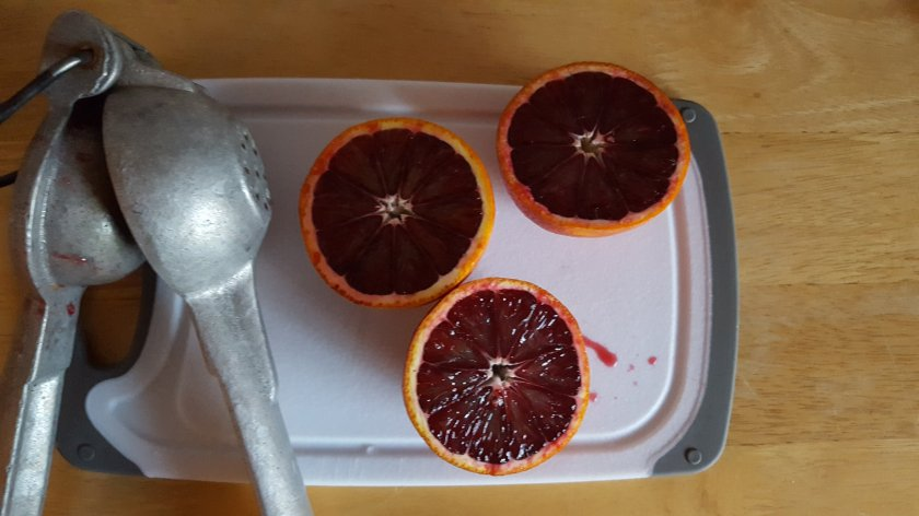 fresh cut blood oranges and juicer