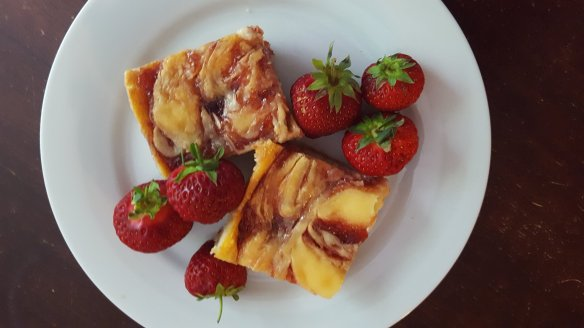 cheesecake bars with swirled strawberry and fresh strawberry garnish on a white plate