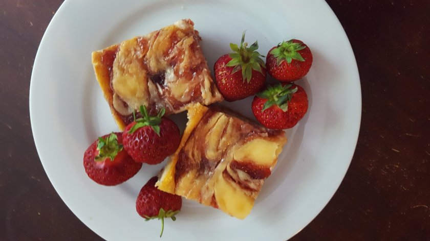 cheesecake bars with swirled strawberry and fresh strawberry garnish on a white plate