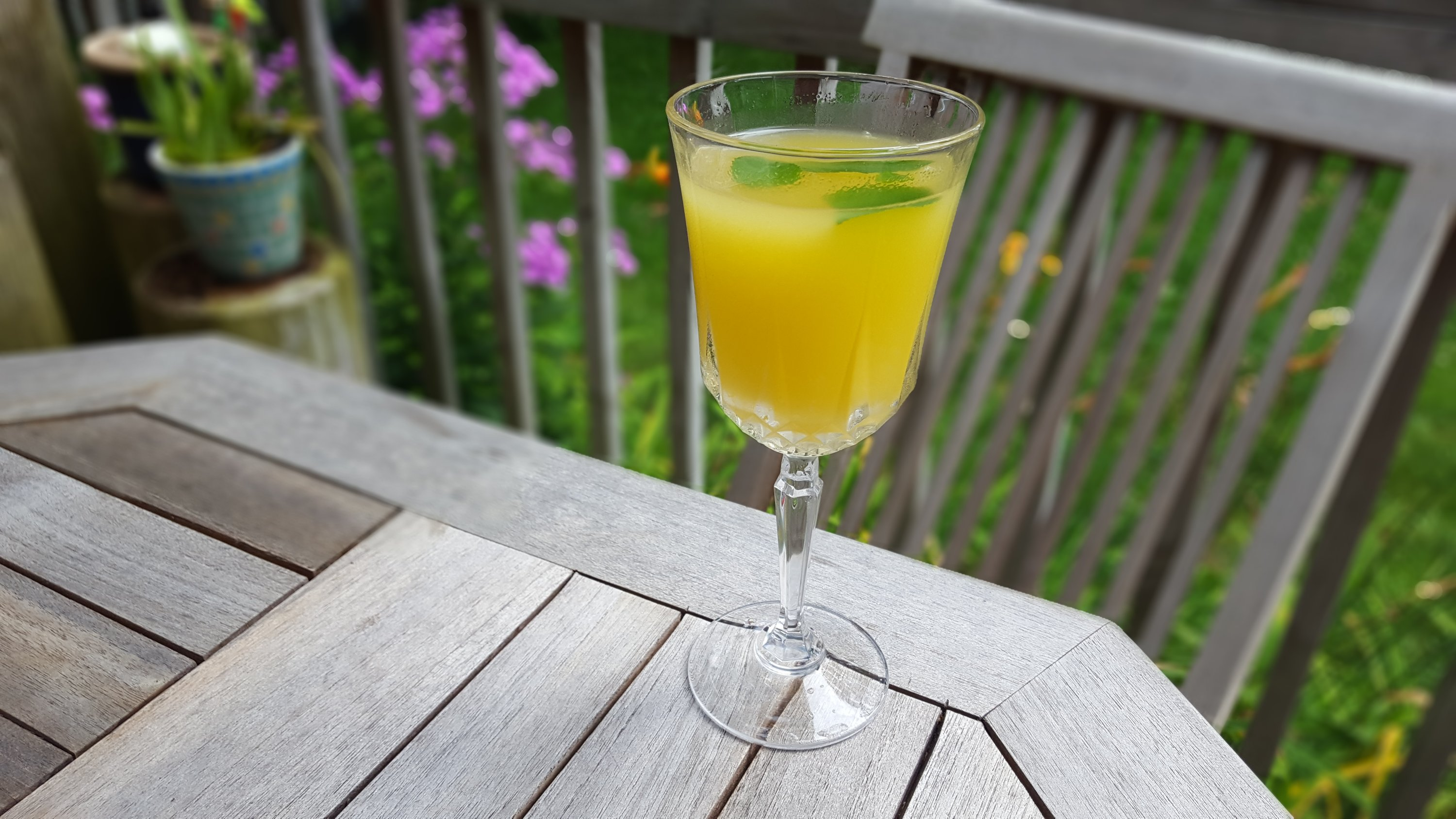 pineapple cocktail with mint and ginger served in a wine glass on a porch in the summertime