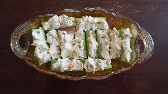 celery stuffed with cream cheese and olives in a fancy orange dish